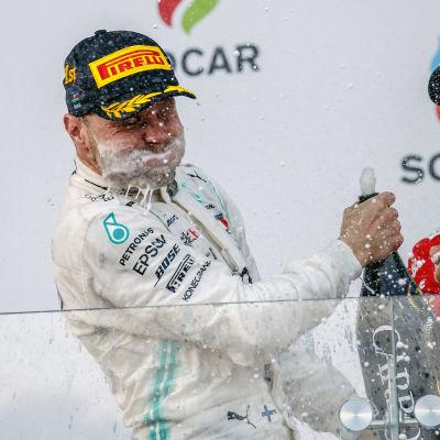 Sebastian Vettel skrattar åt Valtteri Bottas med champagne runt munnen och en flaska i handen.