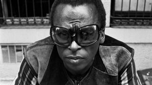 Miles Davis poseeraa kädet ristissä, ranteessa iso kultaketju ja silmillä suuret aurinkolasit