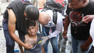 En skadad demonstrant får första hjälp i närheten av Tahrirtorget i Bagdad