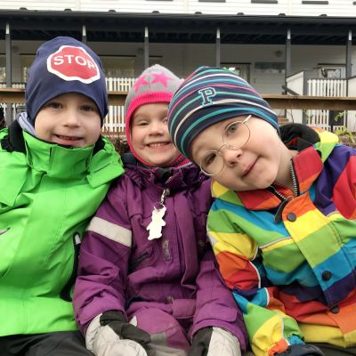 Tre glada dagisbarn utomhus i varma kläder.