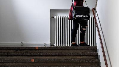En ung person går upp för trapporna iklädd jeans och rutig skjorta.