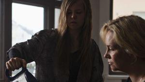 En flicka häller kaffe i en kvinnas, sin mors, mugg vid ett frukostbord.