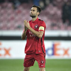 Fotbollspelare i klubbdress klappar i händerna efter match.