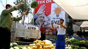 Fruktförsäljare kastar en melon till sin vän framför foto på president Erdogan