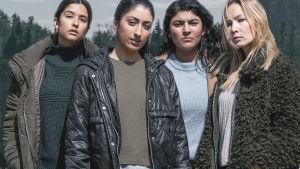 Neljä nuorta naista seisoo vierekkäin ja katsoo kameraan.