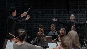 Kapellimestariopiskelija I-Han Fu johtaa orkesteria harjoituksissa. Kapellimestari Hannu Lintu näyttää taustalla mallia