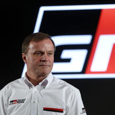 Tommi Mäkinen kuvattuna lavalla Toyota Gazoo Racingin logo takanaan.