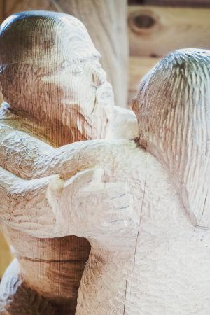Puuveistos joka esittää pyöreähköä miestä ja naista tanssimassa paritanssia.