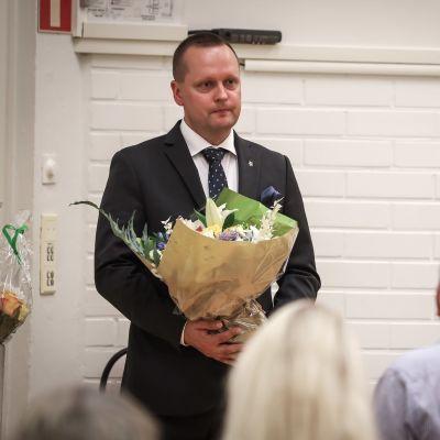 Jarkko Salonen kukkakimppu kädessä.