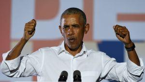 Barack Obama talar stående bakom ett podium klädd i vit skjorta med ärmarna uppkavlade.