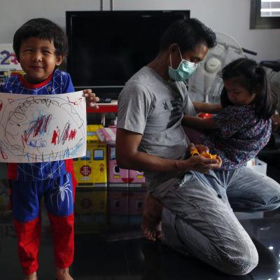 Isä leikkii pienen tyttärensä kanssa perheen kodissa. Heidän vieressään hämähäkkimies-pukuinen poika esittelee piirustustaan kameralle.