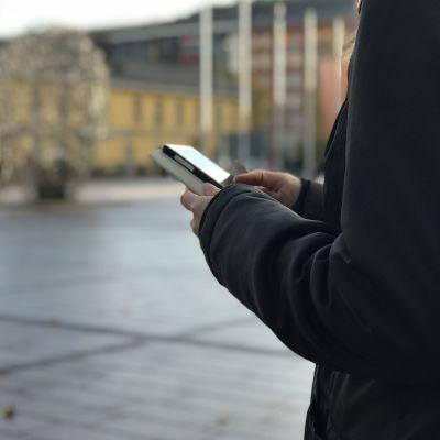 Tjej använder smarttelefon ute