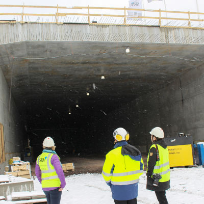 Tre personer står i mynningen till tunneln som är under byggnad, det snöar