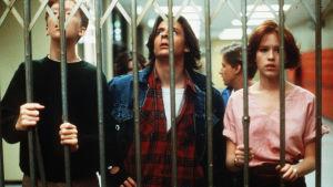 Tre av skådespelarna i The Breakfast Club fångna bakom en gallergrind.