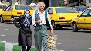 en äldre man och en kvinna iförd ansiktsmask promenerar längs en gata i Teheran