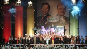 Taiwanesiskt valmöte. Människor på scen viftar med flaggor.