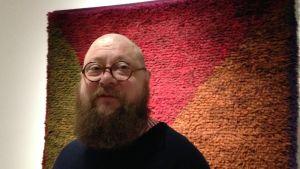 Kurator Juha-Heikki Tihinen och bakom en rya designad av textilkonstnär Uhra-Beata Simberg-Ehrström