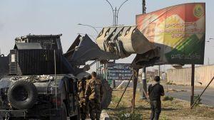 Irakiska styrkor använde en traktor för att ta ner ett plakat med Kurdistans president Massoud Barzani. Bilden togs på måndagen i utkanterna av Kirkuk.