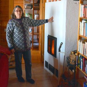 Agneta Glad vid spisen som ger värme.