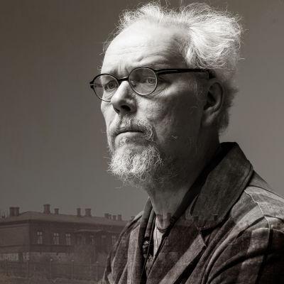 Etualalla silmälasipäinen Juha Siltanen vakavana, taustalla Hämeenlinnan vanhojen kasarmien puiset rakennukset.