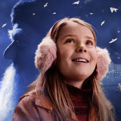 En flicka bland snövall med julgubben i bakgrunden.