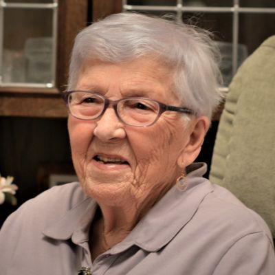 En äldre kvinna med glasögon och grått hår sitter framför en bokhylla och ler.