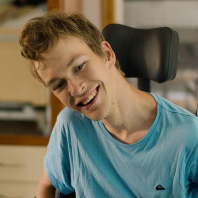 Miika Snellman istuu pyörätuolissaan ja hymyilee.
