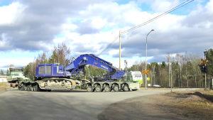 Ett tåg och en transportbil med en grävmaskin på släp.