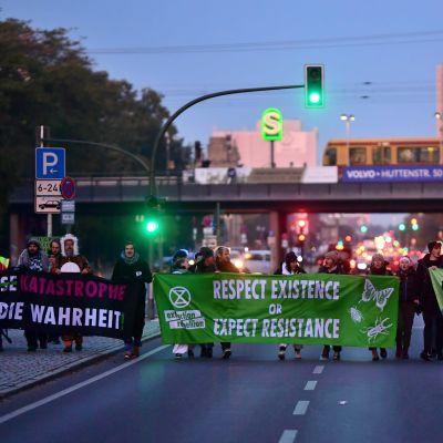 Klimataktivister protesterar genom att blockera en gata i Berlin.
