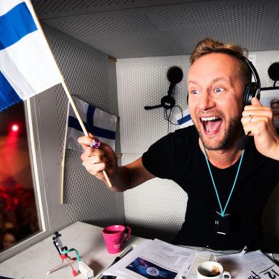 Mikko Silvennoinen selostuskopissa Suomen lippu kädessä.