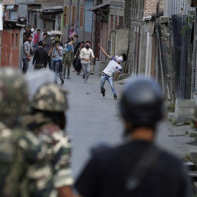 Joukko kapealla kujalla olevia nuoria miehiä heittelee kivillä maastoasuisia turvallisuusjoukkoja. Kuvaaja seisoo sotilaiden takana.