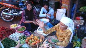 Kvinnor i Malaysia på en marknad. Kvinnorna sitter vid fruktskålar.
