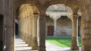 Salamancan yliopiston sisäpihaa reunustava pylväikkö ja pihanurmea.