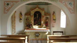 Stämningsfullt altarbord med blommor och ljus.