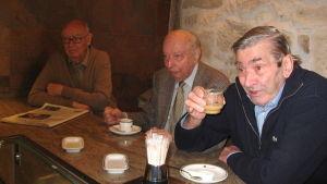 Vanhat miehet juovat kahvia espanjalaisen kahvilan baaritiskillä.