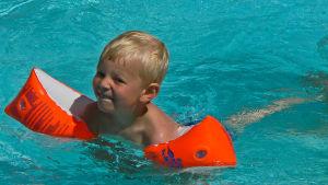 En pojke som simmar i en pool med armpuffar på sig.