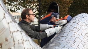Konstnären Stefan Lindfors och svetsaren Kari Hellsberg fäster den tusende Symbiosis-plattan.