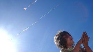 Lapsi. Leijoja taivaalla. Kesä.