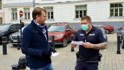 En svensk liberalkonservativ person ger åt en poliskonstapel ett flygblad där det står att estniska homosexuella är välkomna i Sverige.