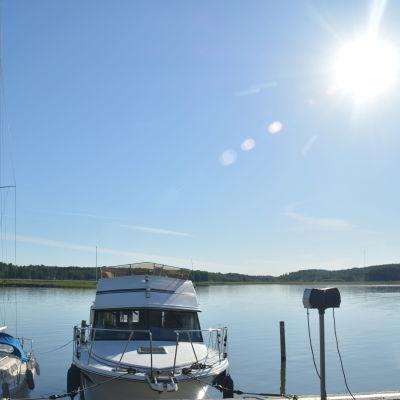 Båtar står förtöjda vid en kaj. Havet ligger platt och solen skiner.