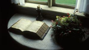 En mycket gammal bok ligger uppslagen på ett bord intill ett fönster.