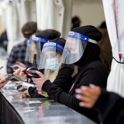 En ung kvinna står vid en utomhusbar på en festival. Personalen bär munskydd och visir.