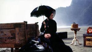 Nainen ja tyttö rannalla mustan aurinkovarjon alla. Anna Paquin ja Holly Hunter elokuvassa Piano.