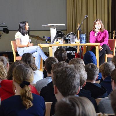 Två kvinnor sitter vid ett bord på en scen. Framför dem sitter en massa högstadie-elever och lyssnar.