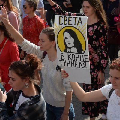 """Minskissä järjestettiin lauantaina rauhanomainen naistenmarssi. Mielenosoittajan kyltissä lukee """"Svjata, valo tunnelin päässä"""". Kyltissä viitataan oppositioehdokas Svjatlana Tsihanouskajaan."""