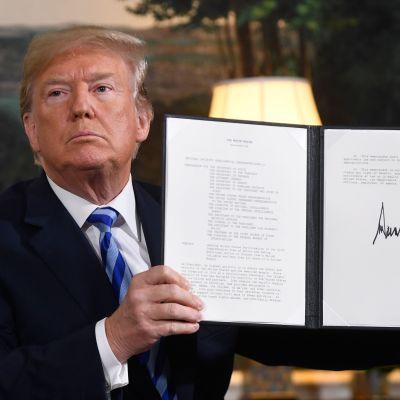 Donald Trump skriver under ett beslut som återinför alla sanktioner mot Iran.