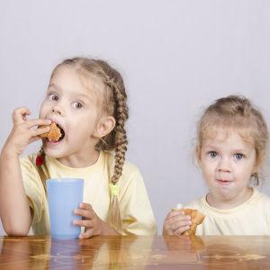 Två barn som äter bulle och ser glada ut. Det ena barnet har också en mugg i sin hand.
