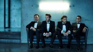 Kent-yhtye istuu ja poseeraa.