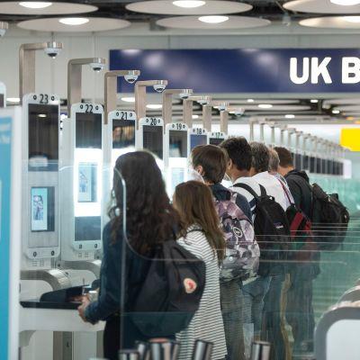Ihmiset tarkistuttavat passejaan rivissä seisovilla automaateilla