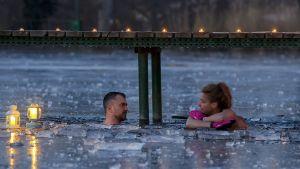 Mies ja nainen ovat avannossa. Jäällä on kaksi lyhtyä luomassa tunnelmaa.